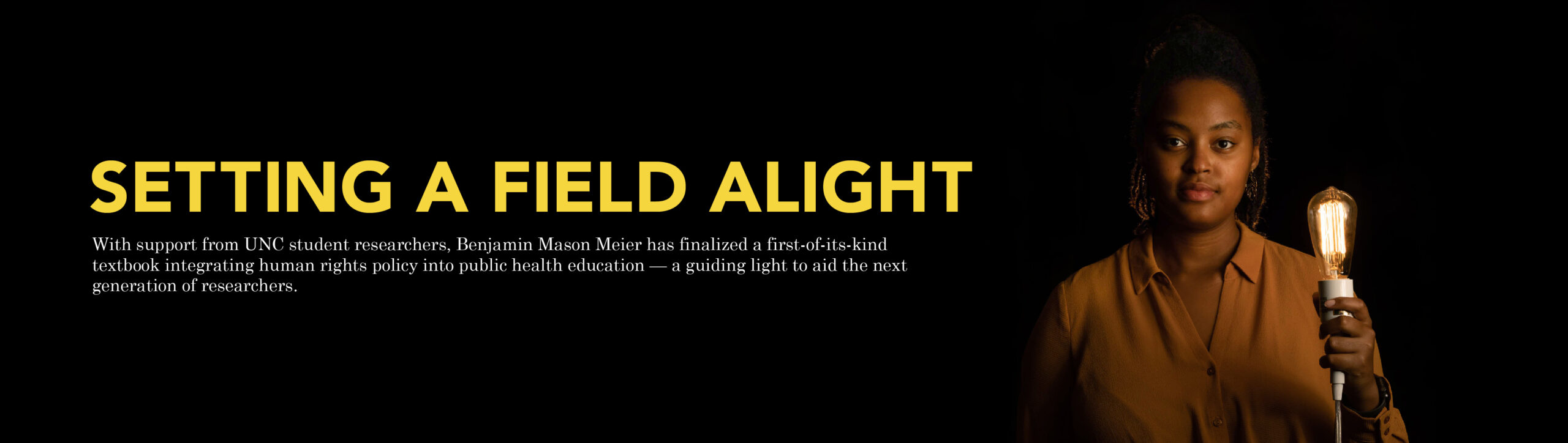 "Main feature banner for the story ""Setting a Field Alight"" with an image of Lenore Hango holding a lightbuld, which is lit-up, illuminating her face . The description for this story reads: ""With support from UNC student researchers, Benjamin Mason Meier has finalized a first-of-its-kind textbook integrating human rights policy into public health education — a guiding light to aid the next generation of researchers."" Click here to read this story."
