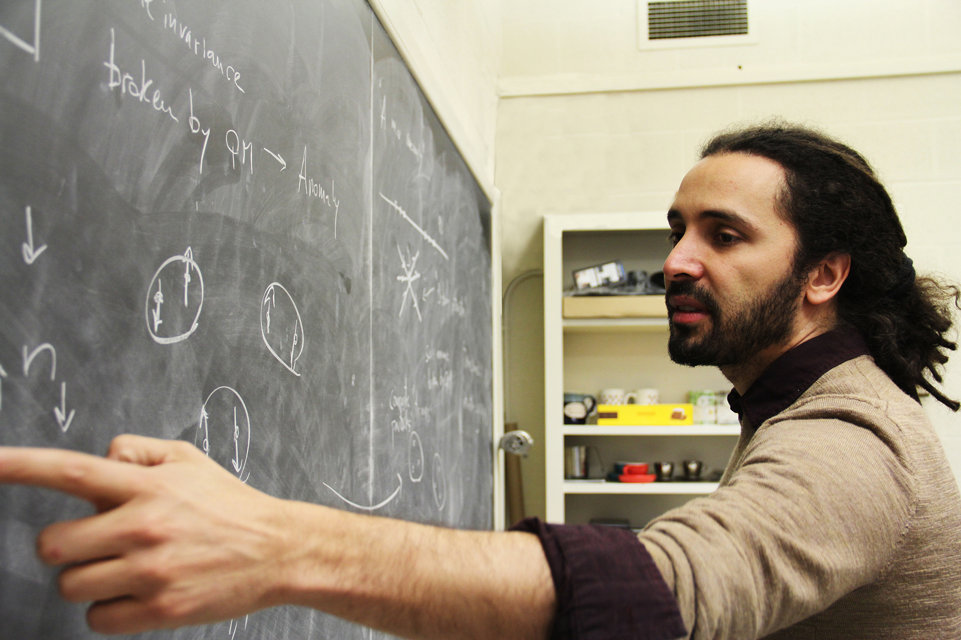 a young male professor points to physics equations on the board
