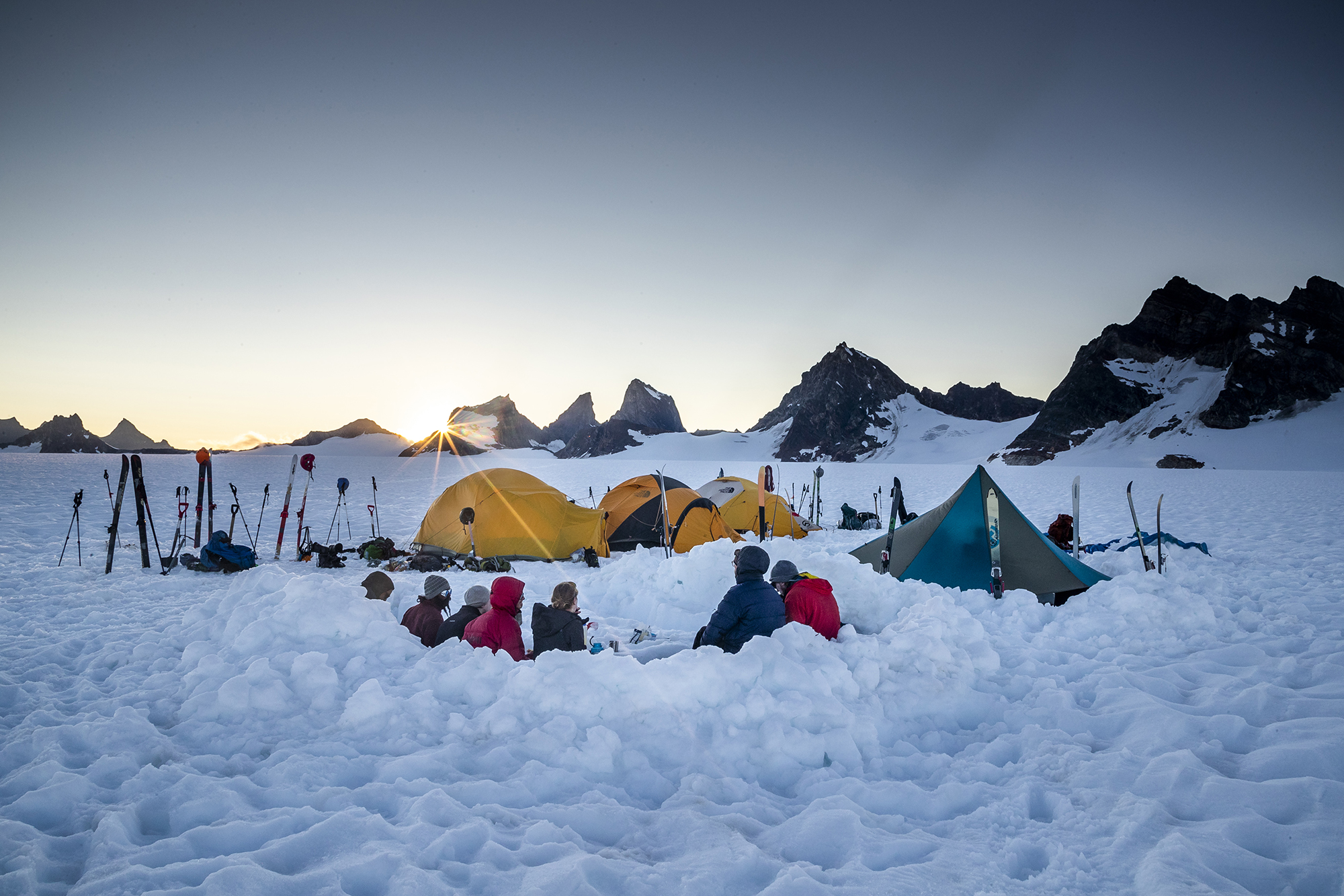 four tents set up in a snowfield in Alaska