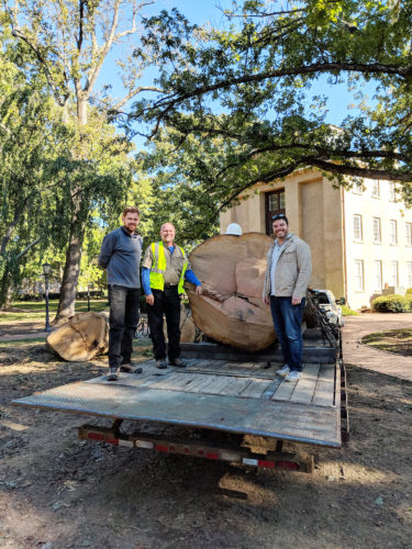 Michael Everheart, Thomas Bythell, and Todd BenDor pose with the post oak after its removal from McCorkle Place.