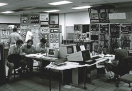 The seated group includes UNC physics professors Tom Clegg and Hugon Karwowski, with their post-doc Chandra Bhat and graduate student Eric Crosson (at far right), during a tandem accelerator experiment in the early 1980s. Standing left at the accelerator controls are TUNL Director Ed Bilpuch (facing the camera) talking with Duke physics professor Russell Roberson.