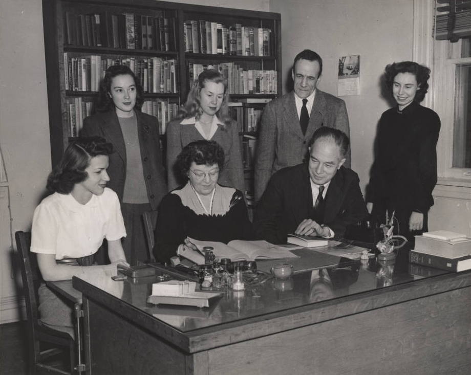 Photo: A woman seated at a desk examines a book. She is surrounded by four women and two men in business attire. Behind them are two large bookshelves.