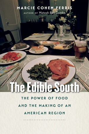 "Cover of ""The Edible South"" by Marcie Cohen Ferris showing a photograph of an elegantly set dinner table. In the foreground is a plate with a slice of ham and greens."