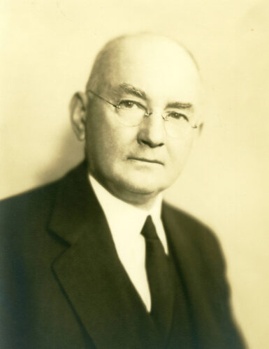 Photograph: A sepia-toned portrait of a man wearing a white shirt, black suit and tie, and glasses.