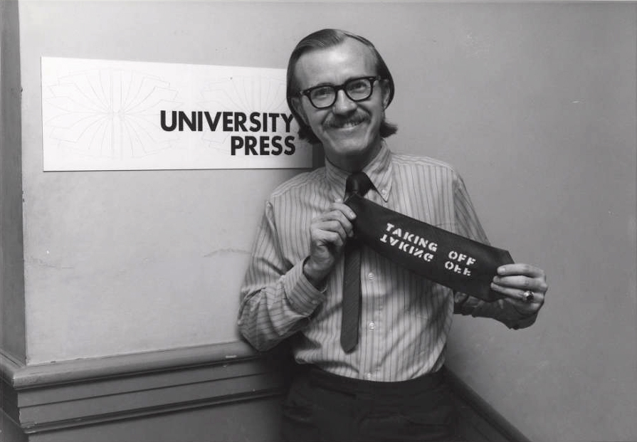 Photo: A smiling man in 1970s-era attire holds up his necktie, which has been stenciled with the words 'Taking Off.' He stands in front of a sign that reads 'University Press.'