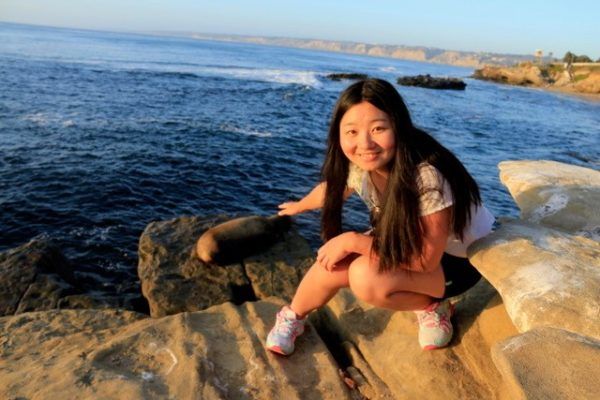 20-something asian girl on beach with sea lion